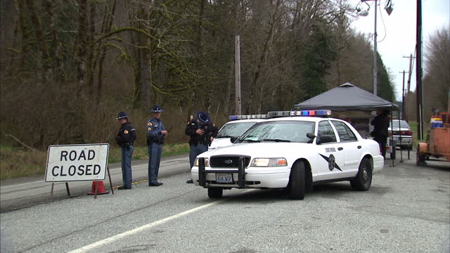 exterior shots police state troopers standing talking next to road closed sign as lorry passes in direction of mudslide scene on 27th march 2014 in... - oso washington stock videos & royalty-free footage