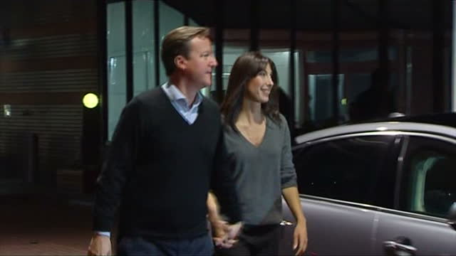 Exterior shots Prime Minister David Cameron gets out of car walks around to open the car door for his wife Samantha both walk into conference...