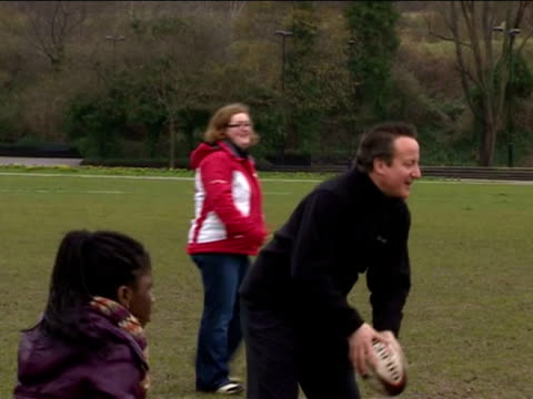 Exterior shots Prime Minister David Cameron passes arugby ball around with a group of children during an event to promote sport finding in schools at...