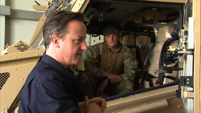 exterior shots prime minister david cameron walks with senior british army officers at camp bastion past military vehicles. interior shots david... - foxhound stock videos & royalty-free footage