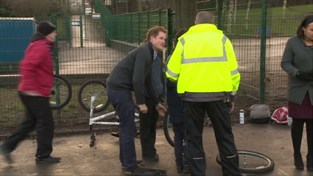 nottingham exterior shots prince harry speaking to child changing bicycle tyre in playground - contea di nottingham video stock e b–roll
