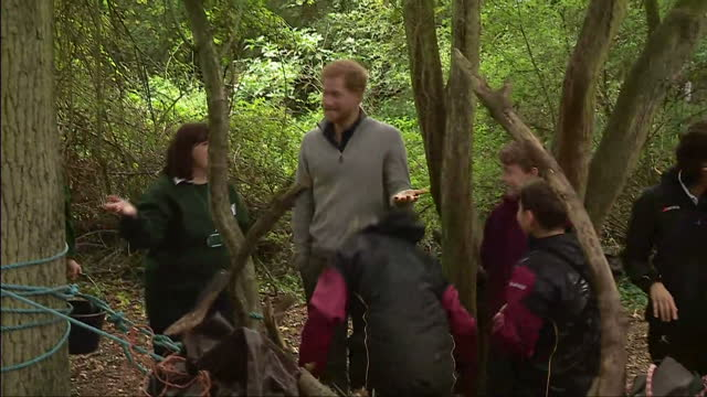Exterior shots Prince Harry talking to children gathered around woodland shelter watching as bucket of water is thrown over shelter with children...