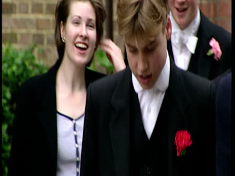 exterior shots prince william at eton dressed in uniform with red carnation in buttonhole he is surrounded by press bows his head and looks shy... - 1996年点の映像素材/bロール