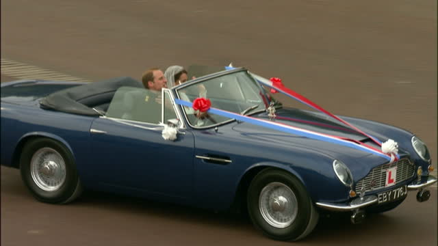 Exterior shots Prince William Catherine Middleton drive out from Buckingham Palace in an Aston Martin DB6 MK11 Volante with a Just Wed number plate...