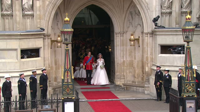 vídeos de stock e filmes b-roll de exterior shots prince william & catherine middleton walk out from westminster abbey holding hands to the sound pealing bells & cheering crowds.... - casamento