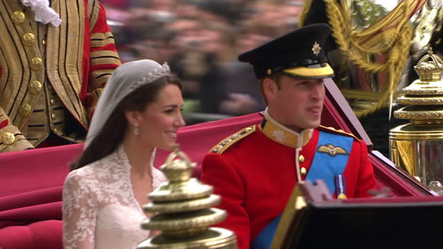 Exterior shots Prince William Catherine Middleton wave to the cheering crowds as they journey from Westminster Abbey in Open State coach along...