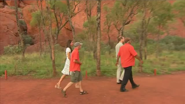 uluru exterior shots prince william duke of cambridge and catherine duchess of cambridge walk at base of ayers rock with guides - visit stock videos & royalty-free footage