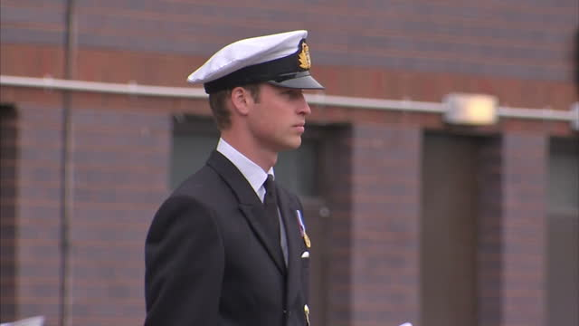 stockvideo's en b-roll-footage met exterior shots prince william prince of wales standing on podium saluting sailors he officially named the base as 'the home of the submarine service'... - meer dan 50 seconden
