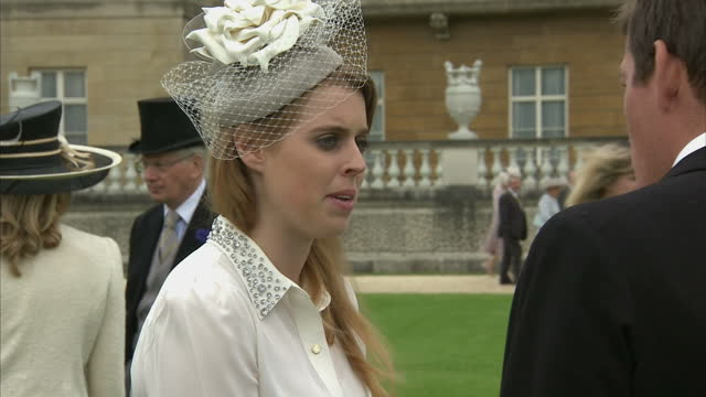Exterior shots Princess Beatrice of York the Queen's granddaughter talking with guests at Buckingham Palace garden party on May 22 2014 in London...
