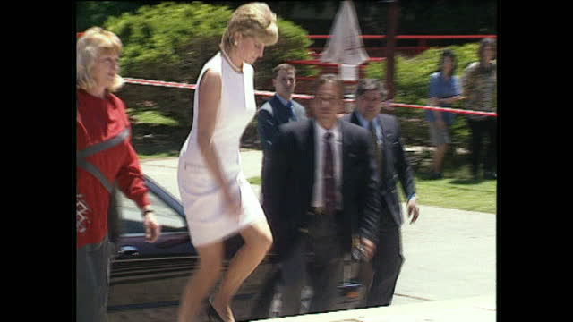 Exterior shots Princess Diana arrives long convoy of security cars and police drive in Princess Diana steps out of car wearing pale pink dress greets...