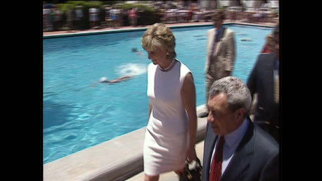 Exterior shots Princess Diana walks with entourage of people including Carlos Menem President of Argentina wearing white dress by pool smiles as she...