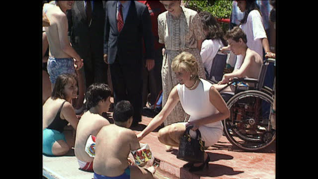 Exterior shots Princess Diana walks with entourage of people wearing white dress talking to young people and swimmers at pool in Buenos Aires...