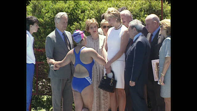 Exterior shots Princess Diana walks with entourage of people wearing white dress talking to people and swimmers at pool in Buenos Aires Argentina on...