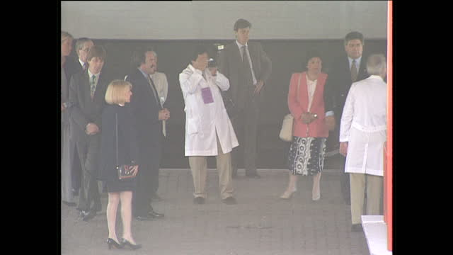 exterior shots princess diana wearing white dress walks out of hospital exit with entourage to cheering crowd waves accepts red book gift from member... - 退院点の映像素材/bロール