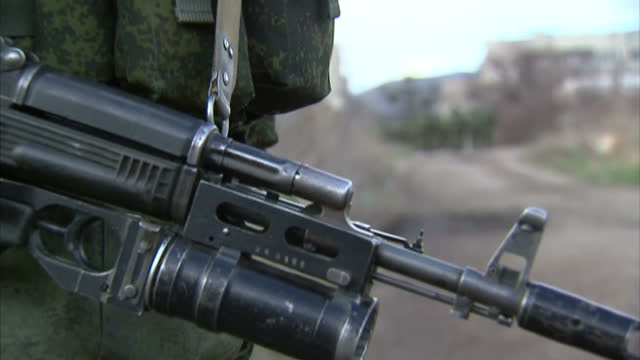 exterior shots pro russian troops standing guard in streets & other troops marching in the background with close up of gun. on march 05, 2014 in... - ウクライナ点の映像素材/bロール