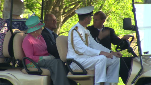 Exterior shots Queen and Prince Philip Duke of Edinburgh take a tour of the gardens at Government House in a solar powered golf cart Queen in...