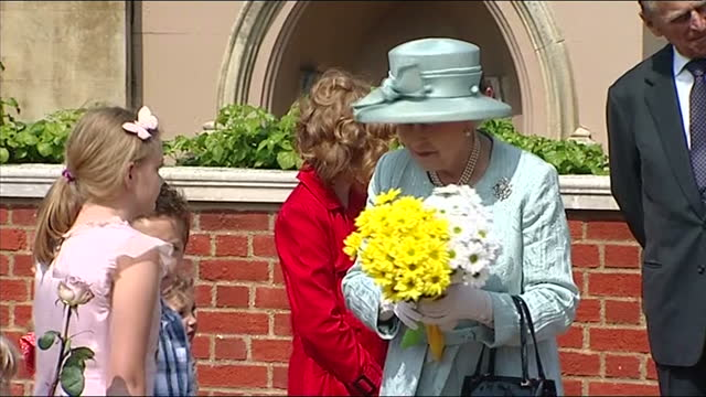 Exterior shots Queen collecting flowers from children then departs in car with Prince Philip Duke of Edinburgh Royal family depart St George's Chapel...