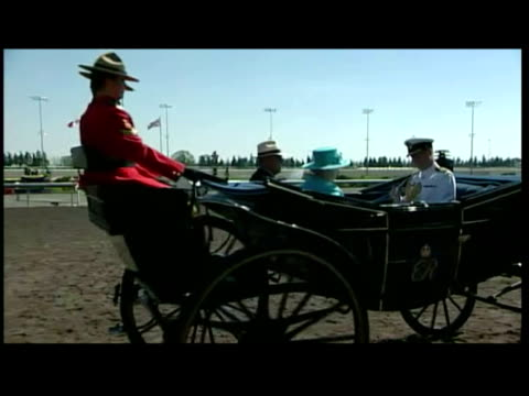 vídeos de stock e filmes b-roll de exterior shots queen elizabeth and prince philip arriving at woodbine racecourse in a carriage pulled by mounties. exterior shots of the queen... - carroça puxada por cavalo