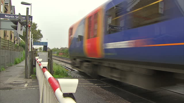exterior shots railway crossing signal flashing warning of approaching train pan from passing train to waiting cars barriers lifting after train has... - railway signal stock videos & royalty-free footage