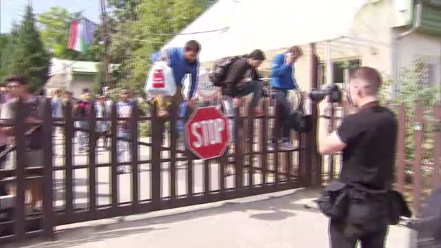 exterior shots refugees migrants asylum seekers clambering over fence escaping holding camp in bicske on september 04 2015 in bicske hungary - ungarn stock-videos und b-roll-filmmaterial