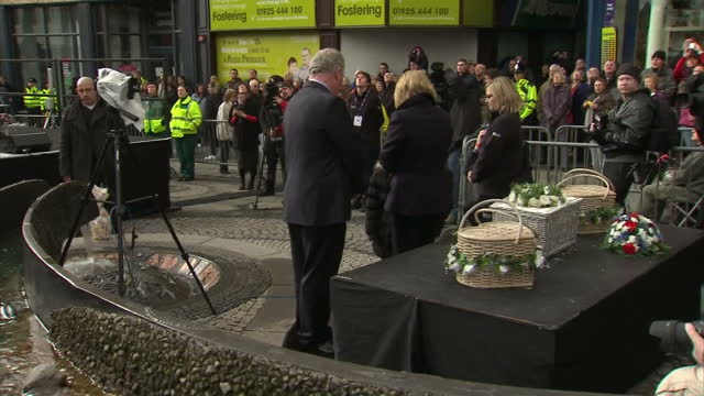 Exterior shots Remembrance service for for two boys killed by IRA bomb people stand by memorial fountain Twentieth Anniversary Of Warrington IRA Bomb...