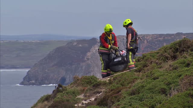 exterior shots rescue workers abseiling down cliff towards car perched on the edge a 56 year old woman has spent the night trapped in a car after it... - abseiling stock videos & royalty-free footage