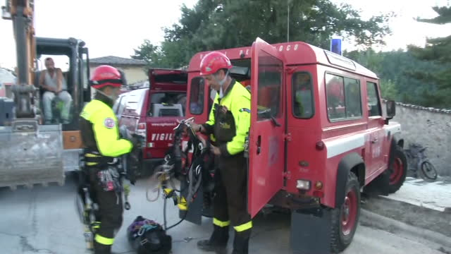 Exterior shots rescue workers preparing equipment before joining search effort to find survivors trapped in rubble remains of houses destroyed during...