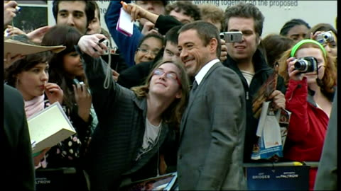 exterior shots robert downey jr, actor, with his wife susan levin, signing autographs on the red carpet for the premiere of iron man at the odeon... - première stock videos & royalty-free footage