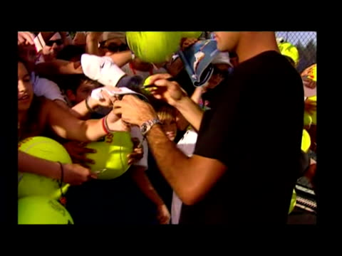 vídeos y material grabado en eventos de stock de exterior shots roger federer wlk from practice court & signing autographs for fans. exterior close ups jim courier smiling into camera. jamie murray... - autografiar