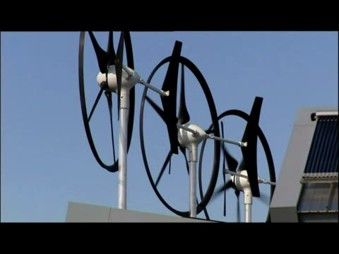 exterior shots rooftops of eco homes with small wind turbines & solar panels. exterior shots jet trails across sky. exterior shots silhouetted... - piccolo video stock e b–roll