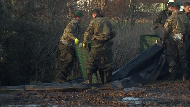 exterior shots royal marines building flood defence barriers for excavators to support with dirt walls. on in somerset, united kingdom. - royal marines stock videos & royalty-free footage