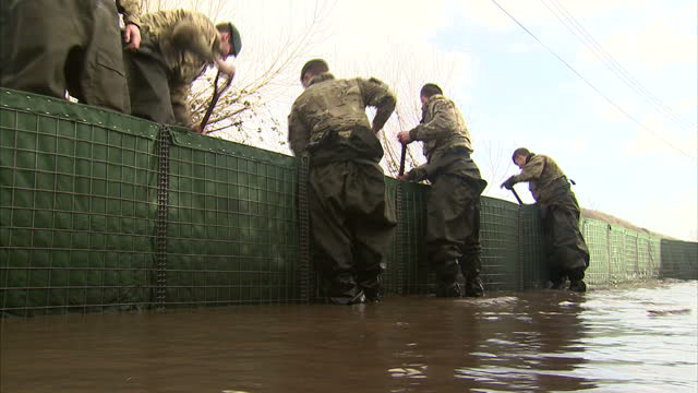exterior shots royal marines filling large flood defences with dirt. on in somerset, united kingdom. - royal marines stock videos & royalty-free footage