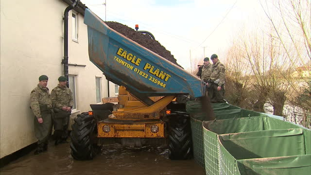 exterior shots royal marines using dump truck to fill flood defences with dirt. on in somerset, united kingdom. - 英国海兵隊点の映像素材/bロール