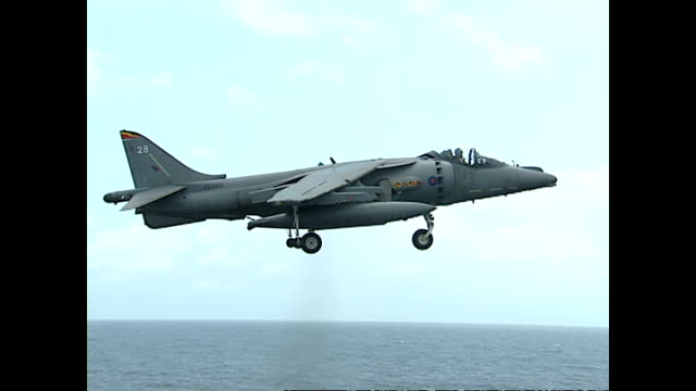 exterior shots royal navy sea harrier fighter jet hovering and completing vertical landing on flight deck of hms illustrious during ukoman joint... - hospital corpsman点の映像素材/bロール