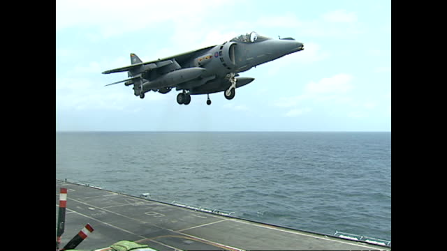 Exterior shots Royal Navy Sea Harrier fighter jet hovering and completing vertical landing on flight deck of HMS Illustrious during UKOman joint...
