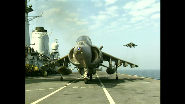 exterior shots royal navy sea harrier fighter jets hovering and completing vertical landings on flight deck of hms invincible aircraft carrier on... - hospital corpsman点の映像素材/bロール
