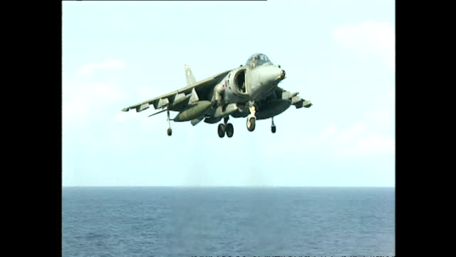 exterior shots royal navy sea harrier fighter jets hovering and completing vertical landing on flight deck of hms invincible aircraft carrier on july... - hospital corpsman点の映像素材/bロール