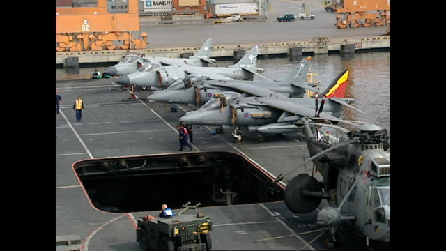 exterior shots royal navy sea harrier fighter jets on flight deck of hms illustrious with armed officers on guard and flight deck and operations crew... - hospital corpsman点の映像素材/bロール