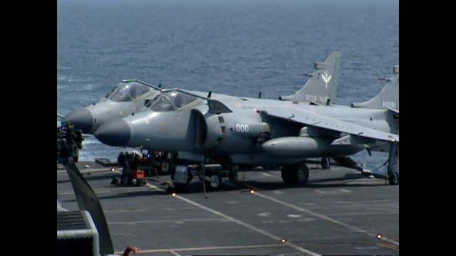 exterior shots royal navy sea harrier fighter jets taking off from flight deck of hms illustrious with flight deck and operations crew working during... - hospital corpsman点の映像素材/bロール