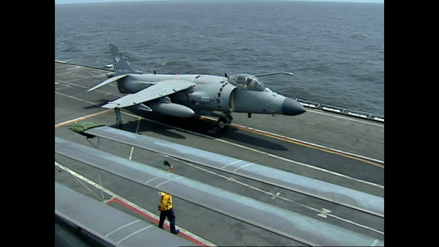 Exterior shots Royal Navy Sea Harrier fighter jets taking off from flight deck of HMS Illustrious with flight deck and operations crew preparing...