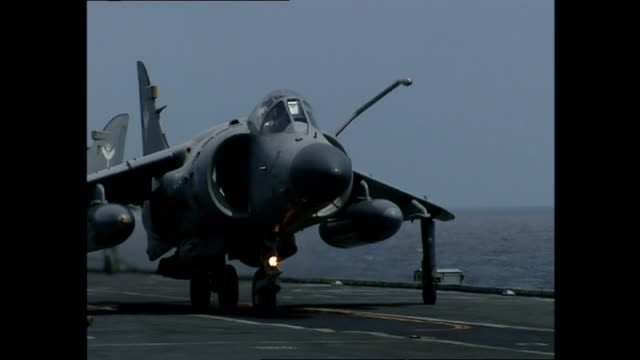 exterior shots royal navy sea harrier fighter jets taking off from flight deck of hms illustrious and sea harrier jet doing low fly past during... - hospital corpsman点の映像素材/bロール