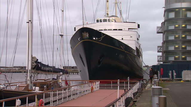 vídeos de stock, filmes e b-roll de exterior shots royal yacht britannia tied up in port listing to one side. exterior shots water pouring from hose out of the yacht. exterior shots... - enviesado
