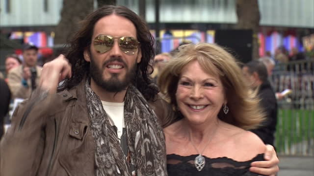 stockvideo's en b-roll-footage met exterior shots russell brand poses with fans for photographs sign autographs before walking the red carpet standing to pose for photo call russell... - signeren
