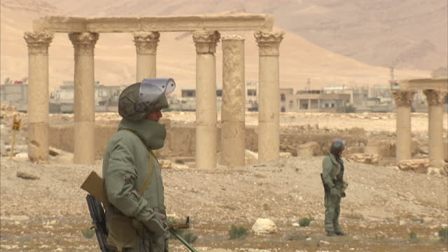 stockvideo's en b-roll-footage met exterior shots russian military bomb disposal team scanning ground in the ancient city of palmyra for hidden bombs and mines left by the islamic... - isis