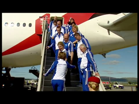 Exterior shots Scottish athletes pose for photcall on plane steps holding the Scottish national flag It's been confirmed all Commonwealth countries...