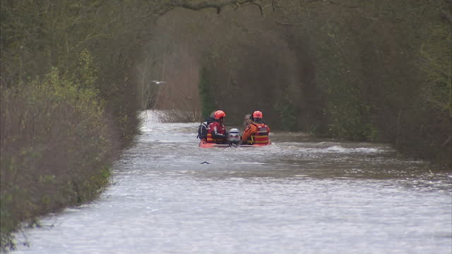 exterior shots search and rescue team in drysuits evacuating marooned people in rib boat, muchelney people rescued in boat in somerset on november... - somerset england stock videos & royalty-free footage