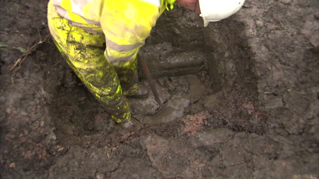 Exterior shots Severn Trent water engineers digging hole in ground with excavator Exterior shots water company workman digging hole to fix leaking...