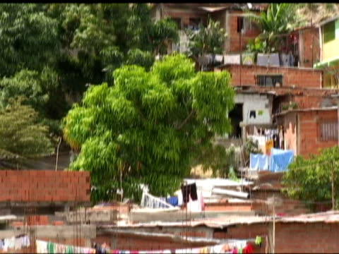 Exterior shots shanty town dwellings Exterior shots street scenes in Caracas with people walking Exterior shot 2 women wave from balcony Exterior...