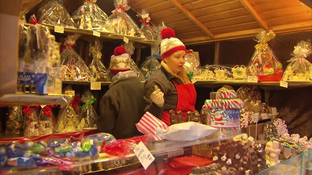 exterior shots shoppers walking around christmas market and buying sweets and chocolate items for sale on market stall on november 20 2016 in chester... - chester england stock videos and b-roll footage
