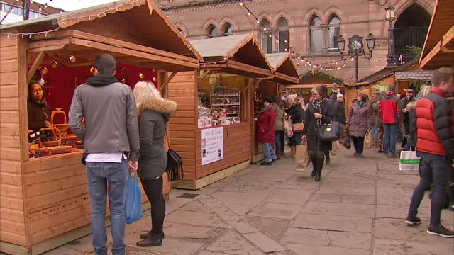 exterior shots shoppers walking around christmas market and viewing items for sale on market stalls on november 20 2016 in chester england - chester england stock videos and b-roll footage